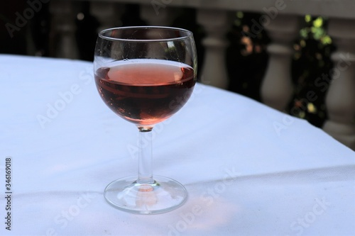Photo Verre de vin rosé dans un verre ballon transparent sur une nappe blanche - Dépar