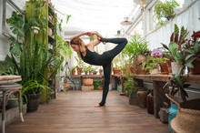 Fitness Home Exercise Concept. A Woman Practices Yoga And Pilates At Home. Eco Friendly House. Urban Jungle And Yoga