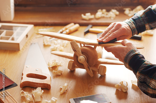 Obraz Craftsman building a wooden toy airplane - fototapety do salonu