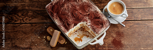 Dish of tiramisu with portion missing and coffee Wallpaper Mural