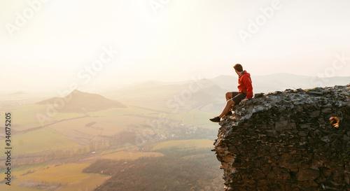 Professional man sitting on castle ruins dressed in active wear resting on peak Wallpaper Mural