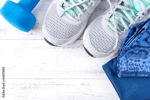 Fototapeta grey sneakers,  blue dumbbell, leggings on a white wooden background top view obraz na płótnie