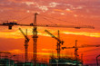 canvas print picture - Tower crane and building construction site silhouette at sunrise.