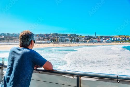 Photo Traveller businessman wearing sunglass enjoys landscape view of Bondi beach, the most famous tourist attraction at Sydney city, Australia