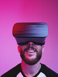 Leinwandbild Motiv vertical portrait of man using VR glasses on colorful gradient background
