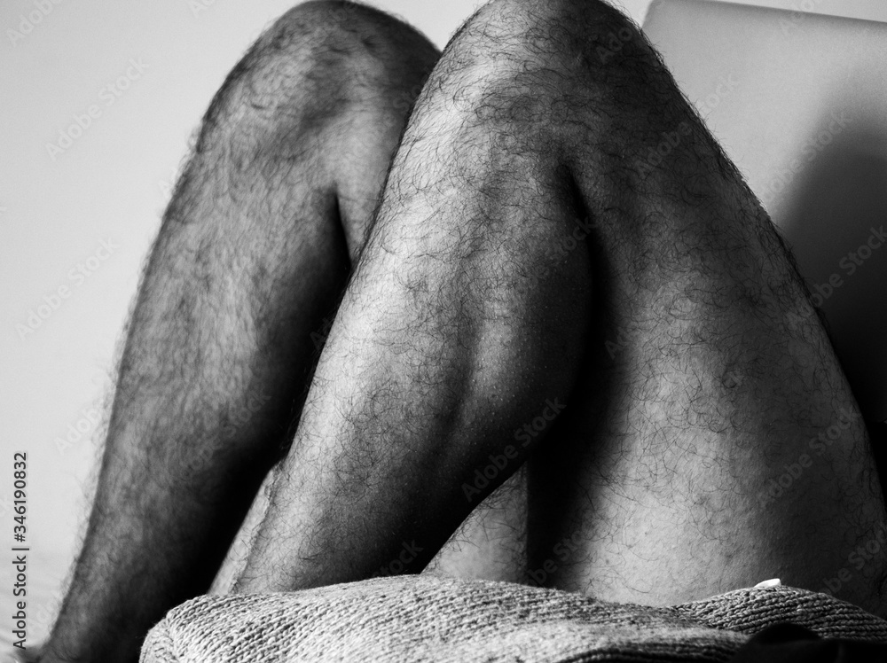 Fototapeta Home working. Black and white picture who depict a man with hairy legs who is chilling or home working on his bed with his computer on his legs.