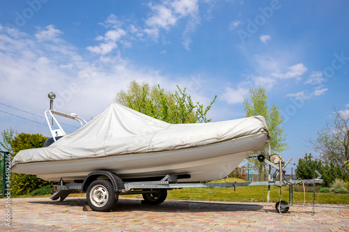 Fotografie, Obraz Big modern inflatable motorboat ship covered with grey or white protection tarp standing on steel semi trailer at home backyard on bright sunny day with blue sky on background