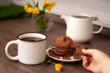 Woman Hands With White Kettle Tea Cup And Choccolate Cookie. Selective Focus. Kitchen Teatime. Time For Rest And Home
