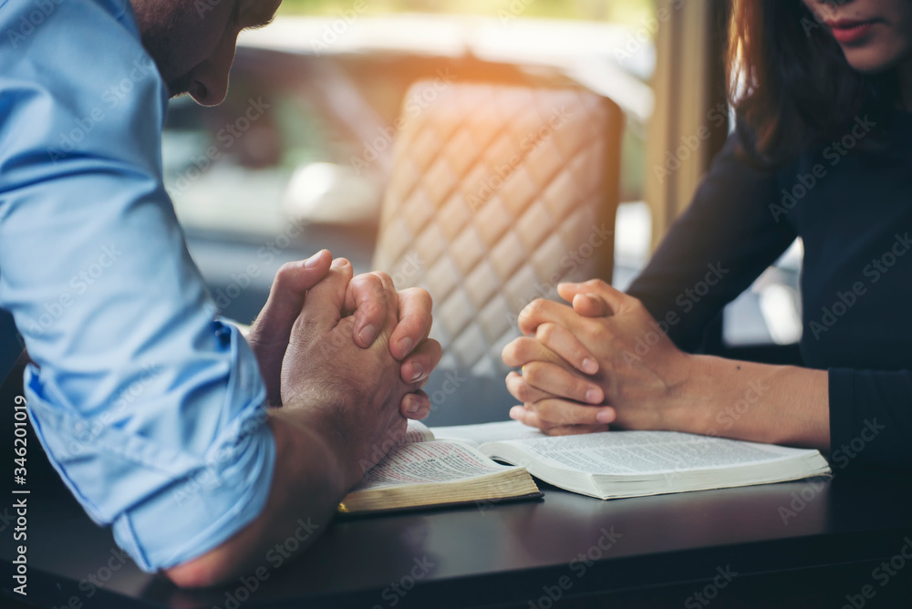 Fototapeta Pray and bible concept. Asian female praying, hope for peace and free from coronavirus, Hand in hand together by woman and Caucasian men, believes and faith in christian religion at church