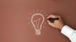 Męska ręka rysuje żarówkę z czarnym markerem