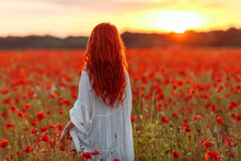 Happy Redhead Woman In White Dress On Field Of Poppies At Summer Sunset