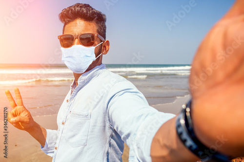 Obraz Young african american man in blue shirt and mask making a selfie portrait on the front camera of a smartphone on the ocean beach - fototapety do salonu
