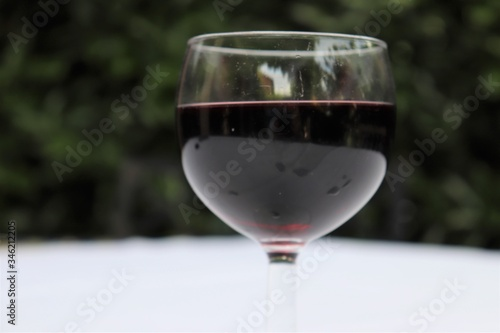 Verre de vin rouge dans un verre à vin transparent sur une nappe blanche - Dépar Wallpaper Mural