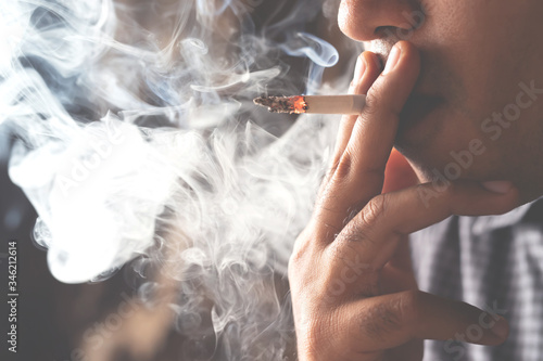 Fototapeta asian man smoking a cigarette smoke spread dark background