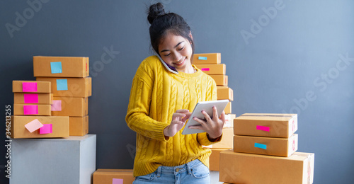 Photo Startup small business SME, Entrepreneur owner using smartphone or tablet taking receive and checking online purchase shopping order to preparing pack product box