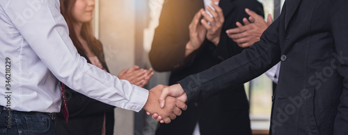 Photo Businessperson handshaking together and colleagues applaud congratulating coworker with promotion in the meeting