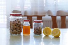 Jars Of Walnuts, Honey, Almond, And Two Slices Of Lemon
