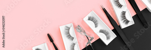 Various tools for eye lash extensions on a trendy pastel pink and black background Fototapeta