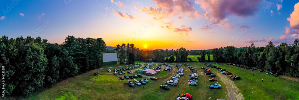 Fototapeta Panorama of outdoor drive-in movie theater at sunset with cars parked in field. Aerial photo taken at Northfield Drive-In.