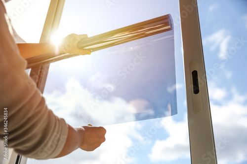 tinted glass in the house. window dimming by dark film. hands apply tint film to the window. tint film on sky background. sky view through tinted glass