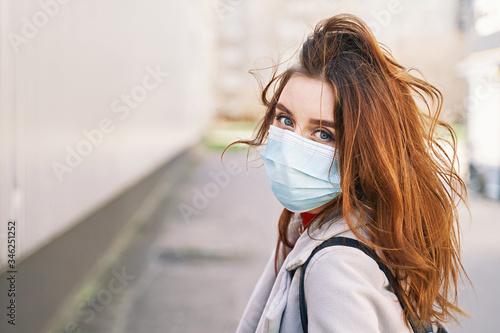 Fotografie, Obraz Young woman with beautiful blue eyes and disheveled hair wearing protection face mask against coronavirus MERS-Cov, Novel coronavirus 2019-nCoV