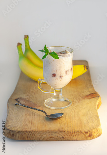 Photo Yogurt Jelly Dessert with banana, strawberry, cocoa, fresh mint in a glass on wooden cut board