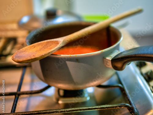 detail of a pot with inside ragu sauce and on top a wooden spoon Fototapeta