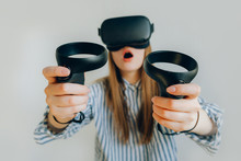 The Young Girl Plays A Game At The Office. Virtual Reality. Vr Glasses. Girl In VR Glasses With Two Joysticks. Girl In VR Glasses On A White Background.