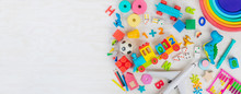 Variety Of Plastic And Wooden Kids Toys On Light Wooden Background With Copy Space