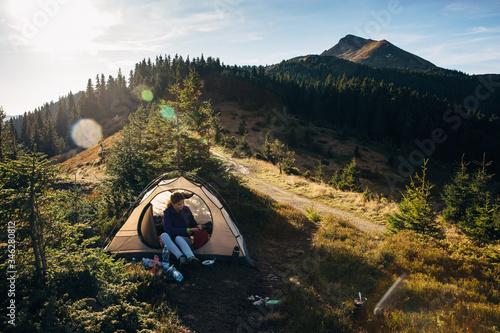 Woman hiker in tent in mountains Fototapet