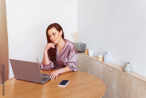 Affectionate woman working home looking on the laptop in the kitchen Wallpaper Mural