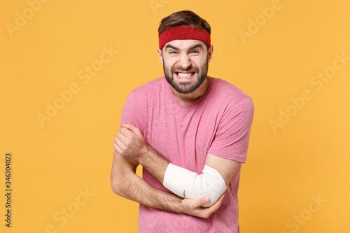 Photo Displeased young bearded fitness sporty guy sportsman in headband t-shirt in home gym isolated on yellow background