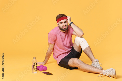 Cuadros en Lienzo Ingured dissatisfied guy sportsman in t-shirt in home gym isolated on yellow background