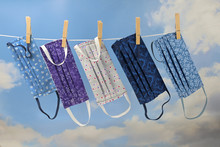Homemade Community Face Masks From Cloth As Protection Against Coronavirus Pandemic Are Hanging On A Clothesline, Blue Sky With Clouds