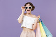 Leinwanddruck Bild - Shocked young woman girl in summer clothes eyeglasses hold package bag with purchases isolated on violet background in studio. Shopping discount sale concept. Mock up copy space. Keeping mouth open.