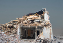 Demolished House Under Big Heap Of Debris, But Some Interior Still Visible Through Torn Down Wall