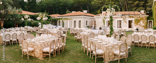 Fototapeta Wedding dinner table reception. Elegant tables for guests with cream tablecloths with patterns, on green lawn, with garlands and chandeliers hanging over them. Chairs with round back obraz