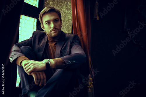 young man sitting on windowsill Fototapet