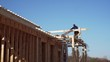 Timelapse, view from below of a builder working on the roof. Frame house building site