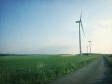 Wind Turbines On Landscape Along Empty Road Against Sky
