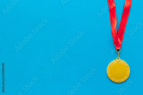 Fotografie, Obraz Gold medal with red ribbon - winner, success concept - on blue background top vi