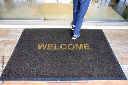 Obraz A welcome mat at the entrance of a cafe restaurant as a customer is seen entering through the front door. - fototapety do salonu