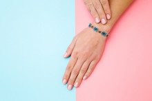 Flower Bracelet On Young Woman Hand Wrist. Pink And Blue Table Background. Pastel Color. Closeup. Top Down View. Two Sides.