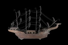 Closeup Shot Of An Old Ship Statue Isolated On The Black Background
