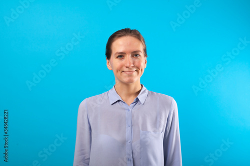 Valokuva Smiling business woman dressed in a blue business shirt posing on a blue background