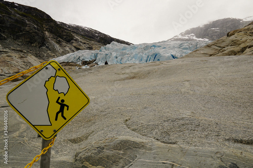 Photo Yellow sign for danger of falling seracs on Nigardsbreen glacier in Norway