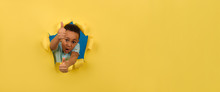 African-American Boy On Yellow Background Of Torn Paper Shows Positive Hand Sign, Finger Up Or Thumb Up, Gesture Of Approval Or Like, Showing Bursts Of Positive Emotions. Concept Of Recommendation