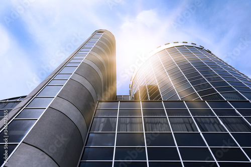 Modern skyscraper with tinted windows against blue sky, low angle view. Building corporation