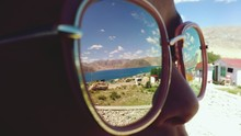 Close-up Of Woman Wearing Sunglasses With Reflection Of River And Mountain