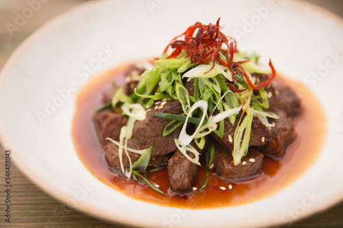 Photo Beef Stir Fry with spring onion and saffron, close up, Grilled beef with onion a